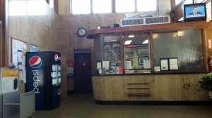 The ticket window.  Notice the signs!  The TV, soda machine, and baggage scale are very recent additions - they weren't there when I first started traveling to visit Alex.